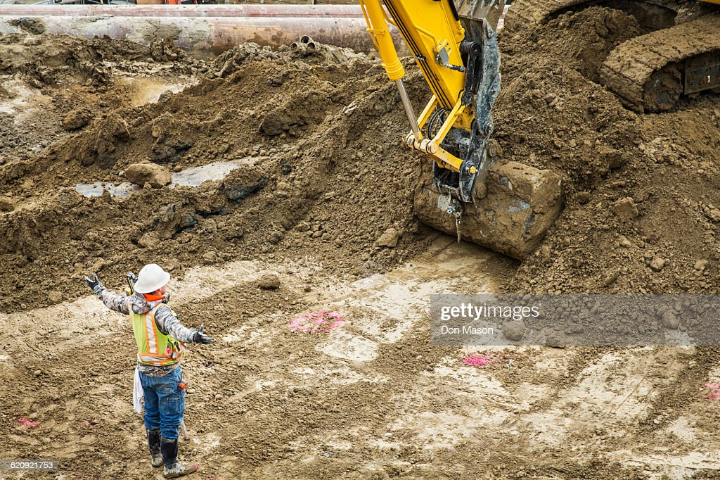 Caucasian worker directing digger at construction site : Stock Photo
