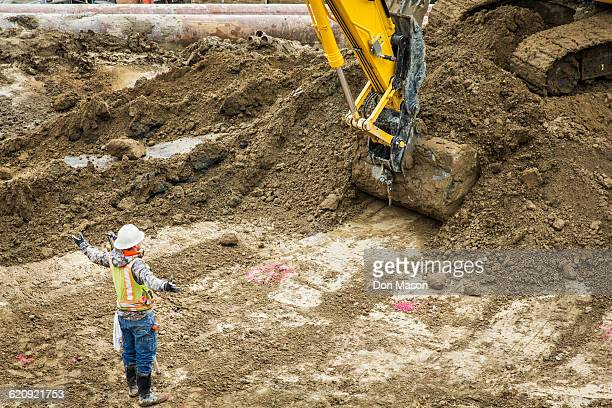 Caucasian worker directing digger at construction site