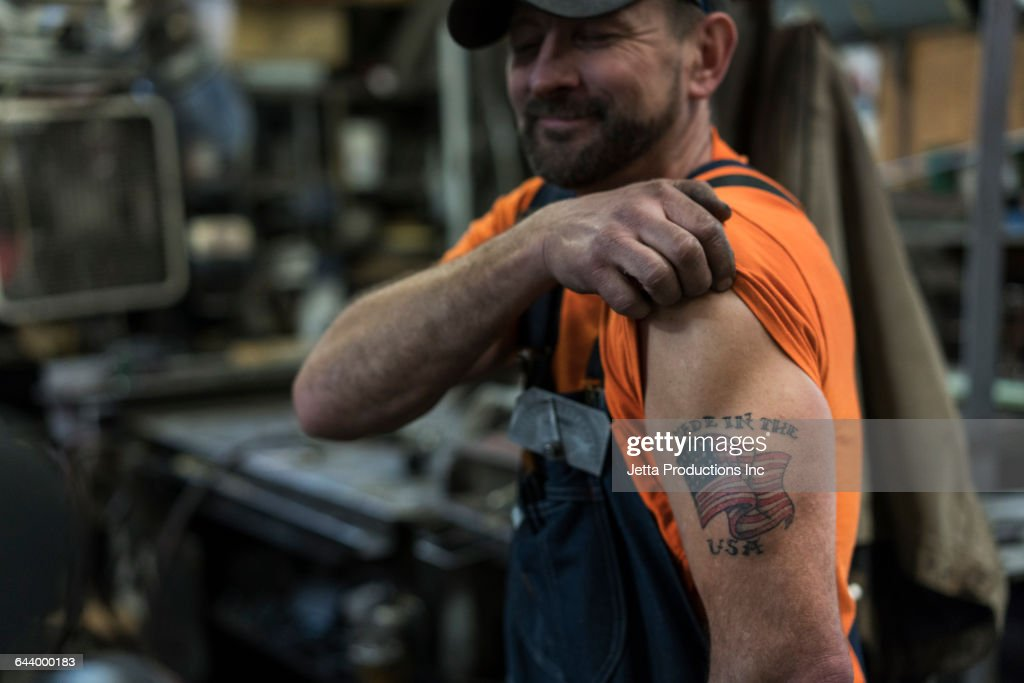 Caucasian worker displaying tattoo in factory : Stock Photo