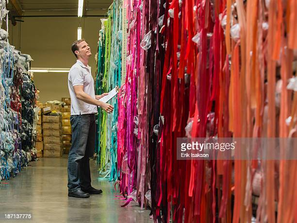 Caucasian worker examining fabric in textile factory