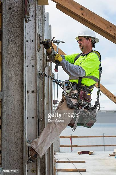 caucasian worker hammering nails at construction site - safety harness stock pictures, royalty-free photos & images