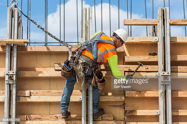 caucasian worker hammering wood at construction site - safety harness stock photos and pictures