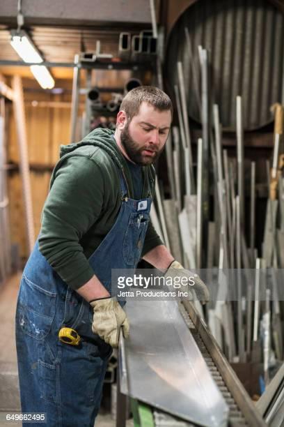 Caucasian worker hauling sheet metal in workshop