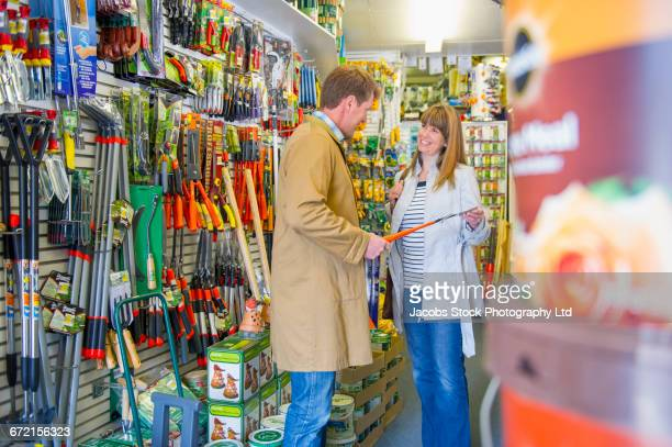 Caucasian worker helping customer in hardware store
