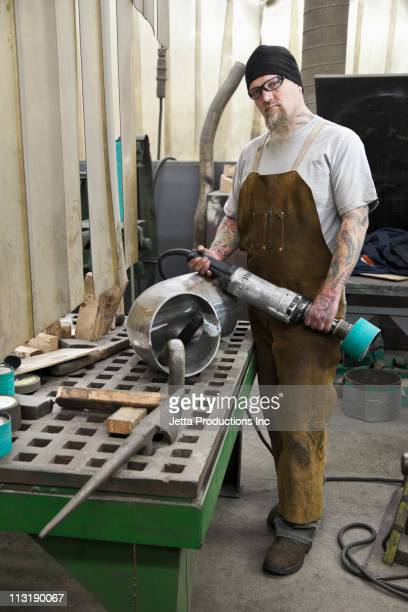 Caucasian worker holding equipment in factory