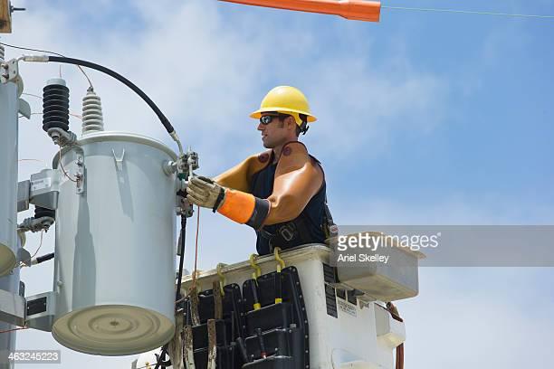 Caucasian worker in cherry picker repairing power line