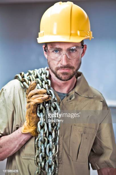 Caucasian worker in hard-hat holding chains