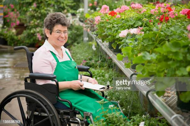 caucasian worker in wheelchair working in nursery - differing abilities female business stock pictures, royalty-free photos & images