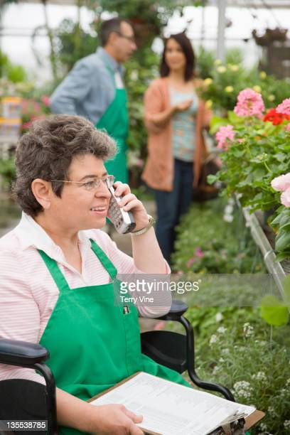 Caucasian worker in wheelchair working in nursery