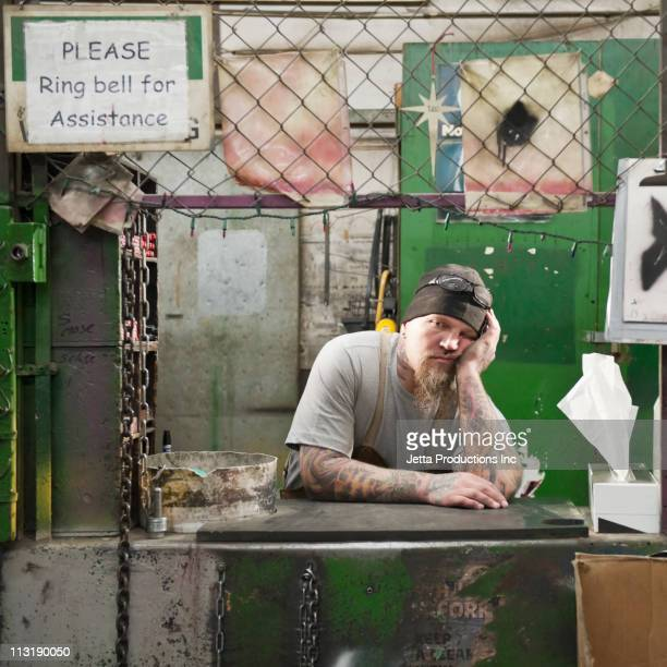 Caucasian worker leaning on counter in factory