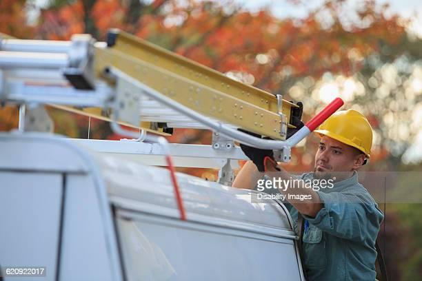 Caucasian worker loading ladder on truck