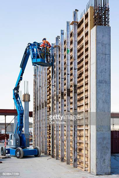 Caucasian worker on boom lift at construction site