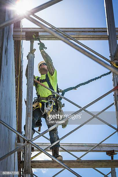 Caucasian worker on scaffolding on construction site