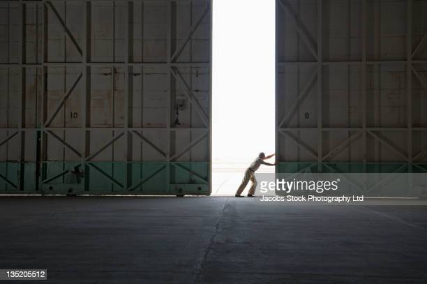 caucasian worker opening large warehouse doors - openmaken stockfoto's en -beelden