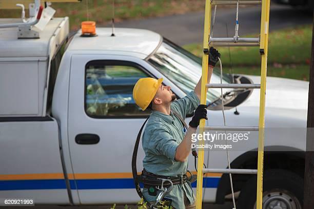 Caucasian worker raising ladder outdoors