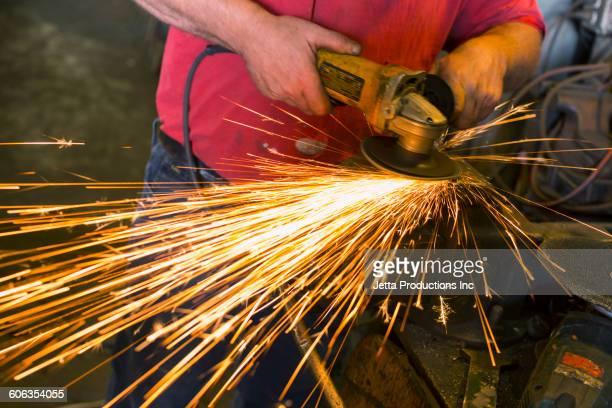 Caucasian worker sanding in factory