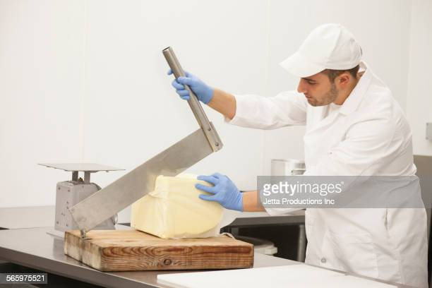 Caucasian worker slicing cheese in factory