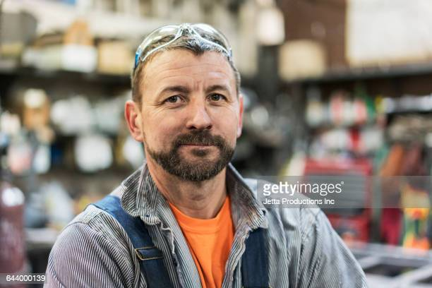 caucasian worker smiling in factory - arbeider stockfoto's en -beelden