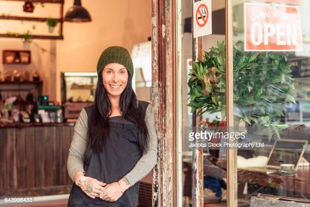 Caucasian worker smiling in store doorway