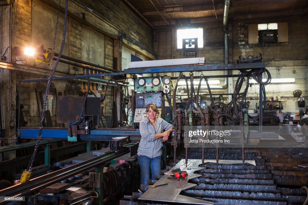 Caucasian worker standing in factory : Stock Photo