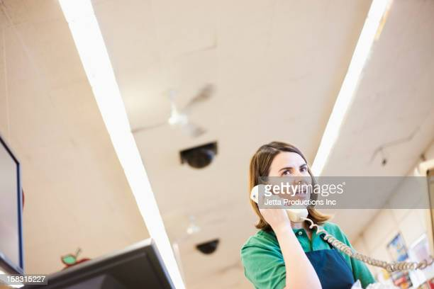 caucasian worker talking on phone in grocery store - intercom stock pictures, royalty-free photos & images