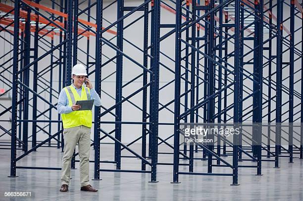 Caucasian worker using digital tablet in empty warehouse