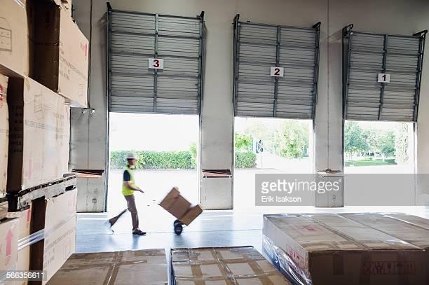 Caucasian worker wheeling cardboard boxes in warehouse