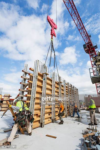 Caucasian workers operating crane at construction site
