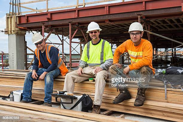 Caucasian workers smiling at construction site