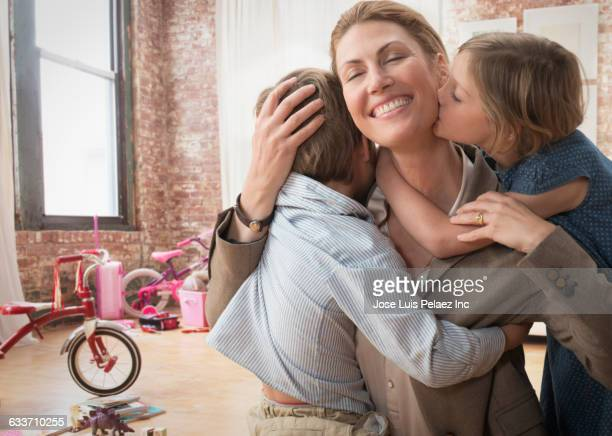 Caucasian working mother greeting children