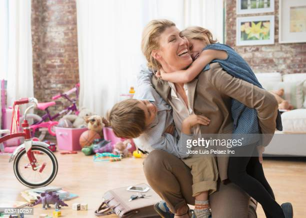 Caucasian working mother greeting children