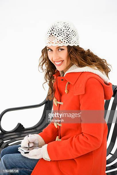 caucasian young adult female in winter clothing sitting on park bench using pda and smiling at viewer. - bilddatenbank stock-fotos und bilder