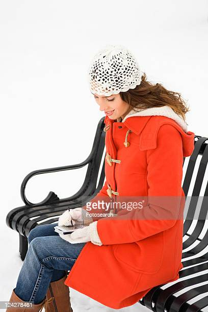 Caucasian young adult female sitting on park bench using PDA.