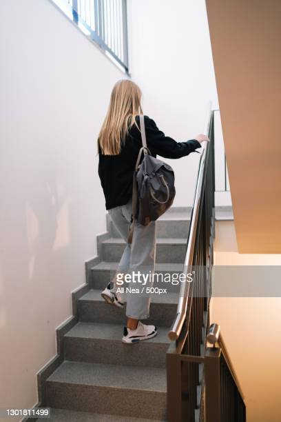 caucasian young adult woman ascending stairs at home,spain - staircase stock pictures, royalty-free photos & images