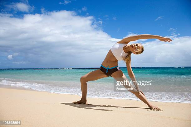 Caucasian young adult woman stretching on beach.
