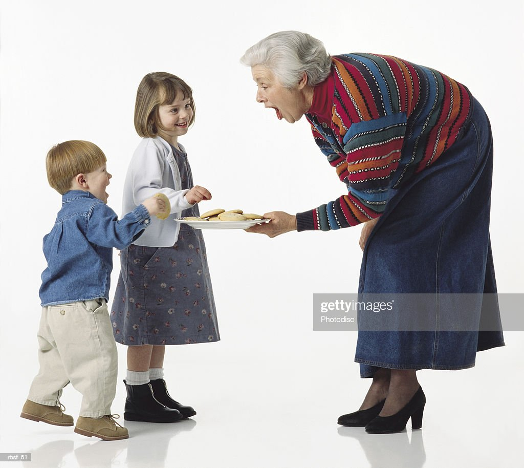 caucasian young kids get cookies from grandma and giggle : Foto de stock