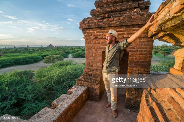 Caucasian young man contemplating the Bagan archeological zone at sunrise, Burma