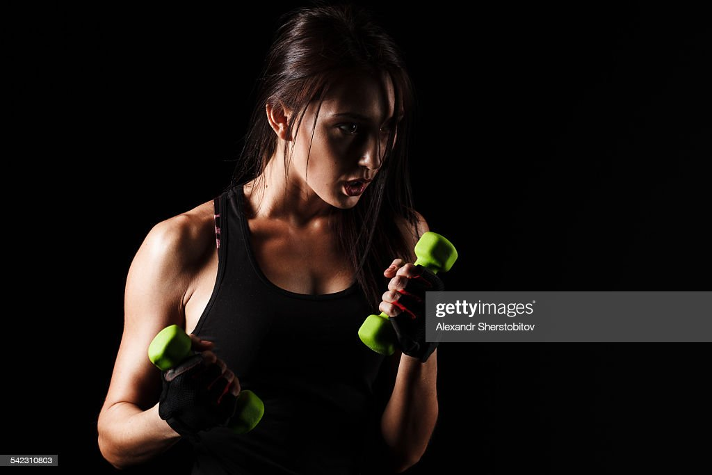 Caucasian young woman boxing with dumbbells : Stock Photo
