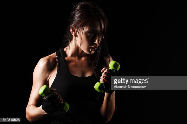 Caucasian young woman boxing with dumbbells