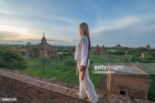 Caucasian young woman contemplating the Bagan archeological zone at sunrise, Myanmar, Asia