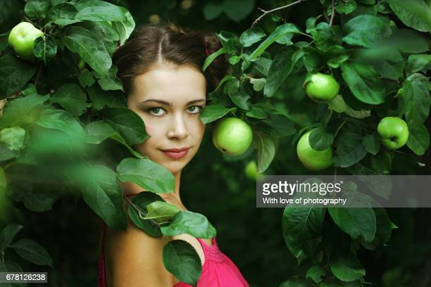 caucasian young woman in apple tree garden, helathy eating, green apples tree, one female