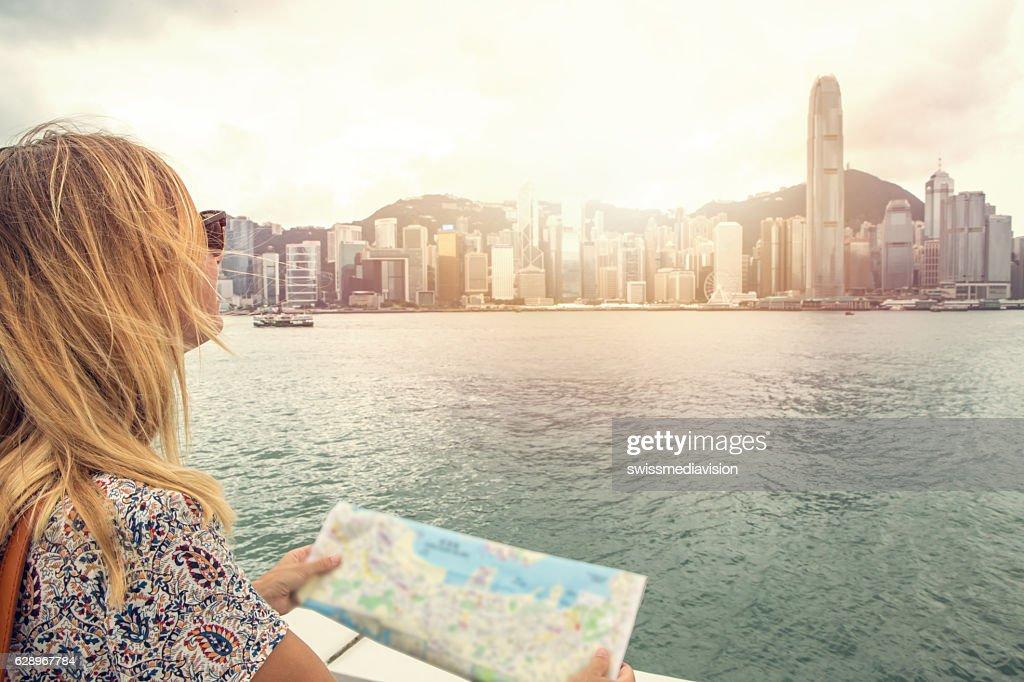 Caucasian young woman looks at Hong Kong city map : Stock Photo