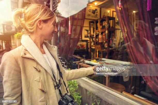 Caucasian young woman window-shopping in China