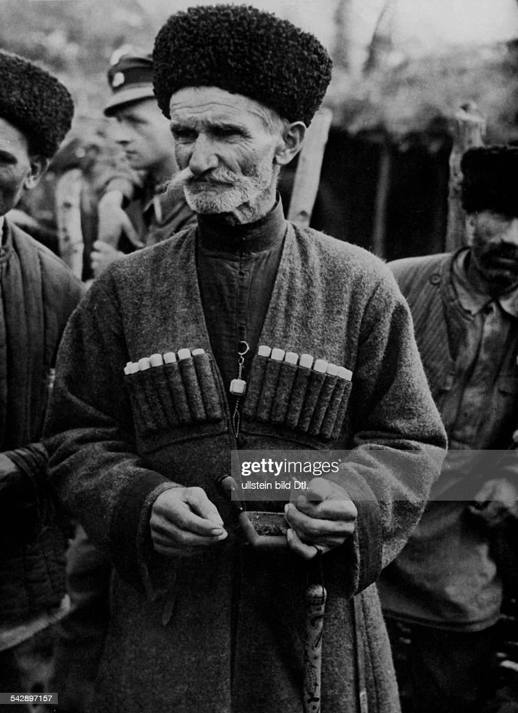 Caucasus Region, population views: A Kabardinian (cerkessian) man in traditional clothing with typical Tscherkeska and Papacha. Background a german soldier, october 1942 : News Photo