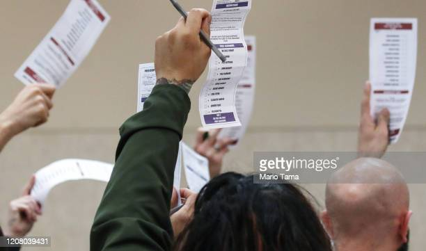 Caucus goers hold up their presidential preference cards at a Democratic presidential caucus site at East Las Vegas Community Center on February 22...