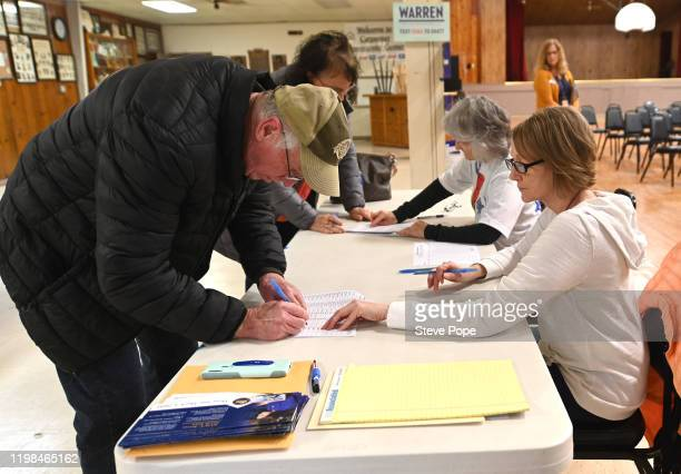 Caucus goers sign in on February 3 2020 in Carpenter Iowa Iowa is the first contest in the 2020 presidential nominating process with the candidates...