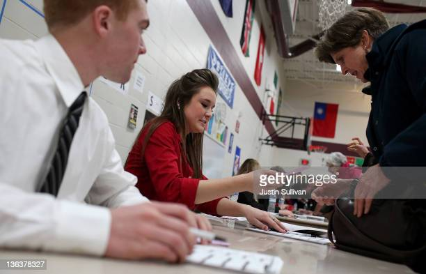 Caucus volunteer Kate Paul registers a voter at the Ankeny 9 Republican caucus on January 3 2012 in Ankeny Iowa Iowans are preparing to caucus to...