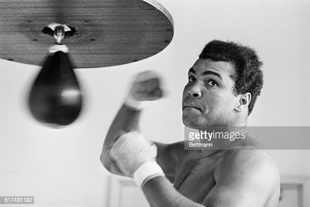 Caught in a rare pose- his mouth shut--Muhammad Ali punches bag here March 31 for his April 1 bout with heavyweight Mac Foster. The ex-champ predicts...