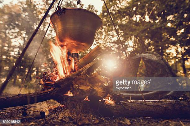 Cauldron on log fire with tent in the background.