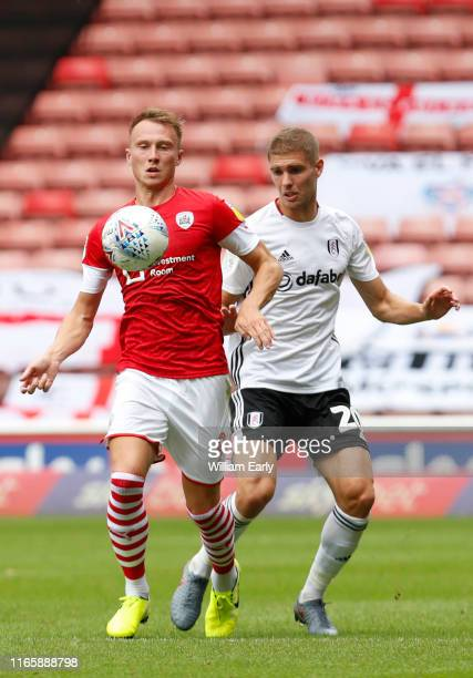 Cauley Woodrow of Barnsley and Maxime Le Marchand of Fulham during the Sky Bet Championship match between Barnsley and Fulham at Oakwell Stadium on...